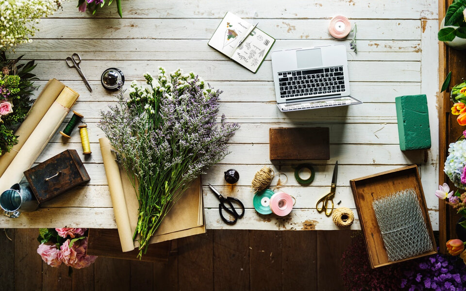 An outdoor table showing craft supplies, a bouquet of flowers, and a laptop.